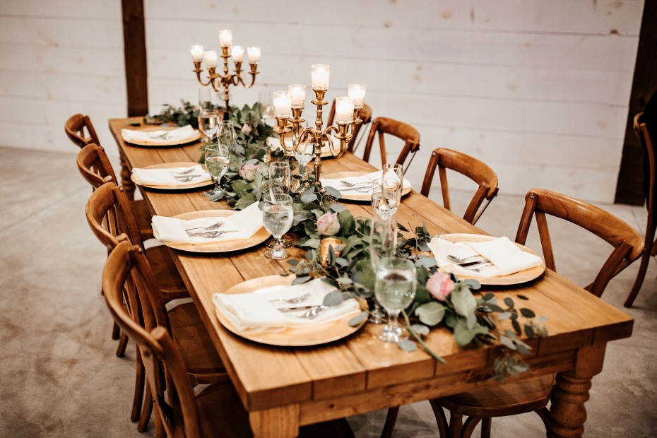 Wood reception table with eucalyptus centerpiece
